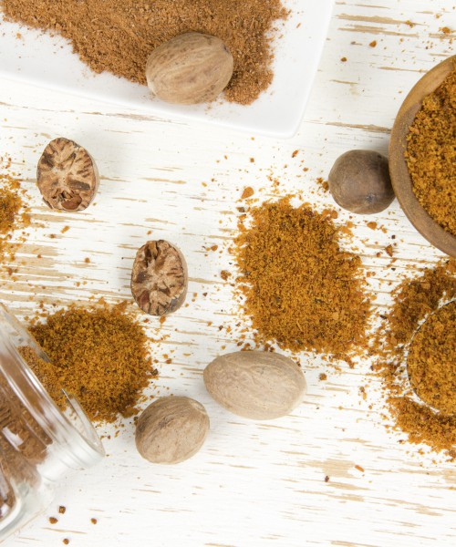 Photo of bowls full of nutmeg spice on white wooden surface