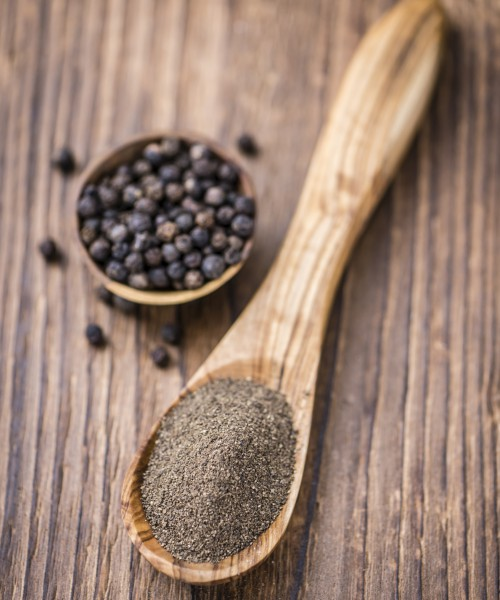 Some fresh milled Black Pepper on wooden background (selective focus; close-up shot)