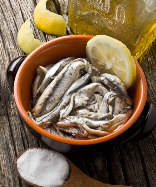 anchovies with olive oil and lemon on a bowl