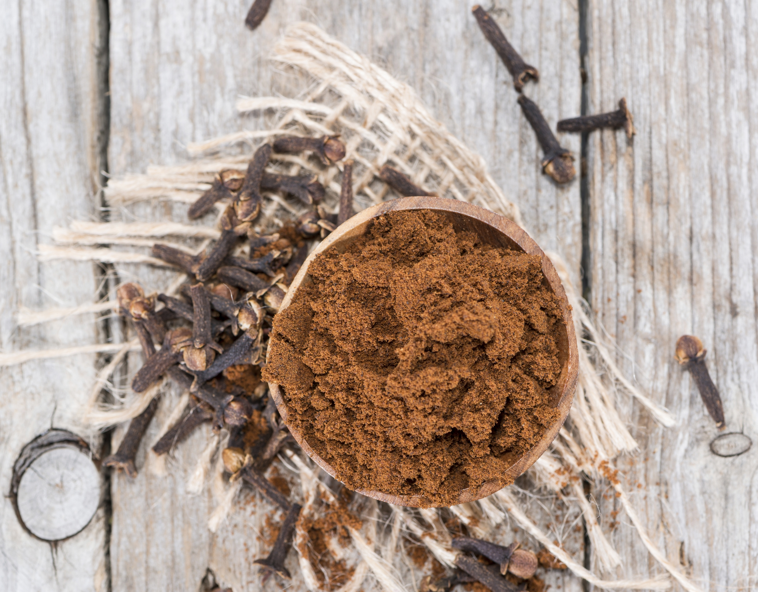 Portion of fresh made Clove Powder on vintage wooden background