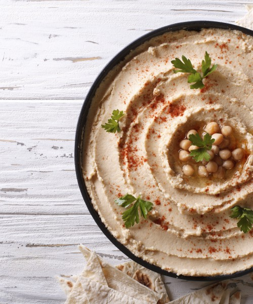 Classic hummus with parsley on the plate and pita bread. horizontal top view